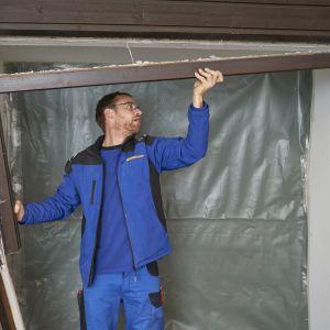 Usuwanie starych drzwi zewnętrznych. Aby stworzyć miejsce pod nowe drzwi wejściowe, trzeba wystawić starą płytę drzwiową, usunąć przeszklenie z elementu bocznego i zdemontować ramę.  Fot. Hörmann