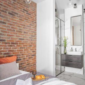 Do wykończenia ścian za kanapą w salonie oraz za łóżkiem w sypialni architekci zastosowali okładzinę  z cegły Milke, która nadała mieszkaniu industrialny klimat.
