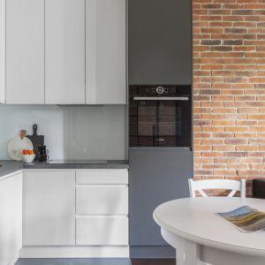 Na tle białej, lakierowanej na półmat zabudowy wyraźnie wyróżnia się słupek, w którym umieszczono piekarnik.