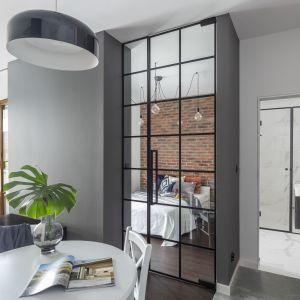 Głównym zabiegiem, który pozwolił architektom Decoroom otworzyć przestrzeń było zastąpienie ściany dzielącej sypialnię i salon szerokimi, sięgającymi sufitu przeszklonymi drzwiami.