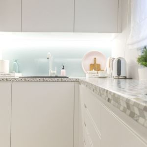 Minimalistyczne białe szkło nad blatem w kuchni. Projekt Katarzyna Czechowicz, pracownia design me too. Fot. Katarzyna Czechowicz