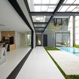 """Na słonecznej Sycylii w domu zaprojektowanym w myśl zasady """"mniej znaczy lepiej"""" królują przeszklenia i przestrzeń, dając pierwszeństwo naturalnemu światłu. To ono tworzy klimat domu. By go utrzymać i podkreślić, architekci postawili na minimalistyczny, bardzo oszczędny spiek Calce Avorio z oferty Laminam, który zastosowali zarówno na posadzce wokół basenu, jak i na jego obudowie, podkreślając tym samym surowy charakter całej przestrzeni."""