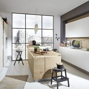 Tradycyjną białą zabudowę kuchenną uzupełnia wyspa w kolorze drewna. Fot. Nolte Kuchen