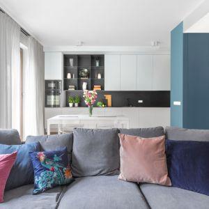 Otwarta kuchnia z jadalnią i salon z kanapą - zwracają uwagę pastelowe akcenty i piękna biała zabudowa kuchenna. Projekt: Decoroom