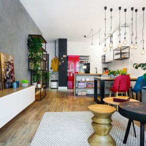 Niewielki salon połączony z kuchnią i jadalnią. Na ścianie imitacja betonu oraz białe cegły, świetne czerwone akcenty kolorystyczne. Projekt Krystyna Dziewanowska, Red Cube Design. Zdjęcia Mateusz Torbus, 7TH IDEA