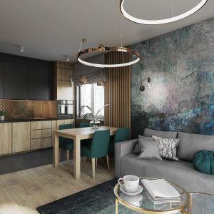 W tym niewielkim, nowoczesnym wnętrzu uwagę zwraca elegancka kuchnia z piękną złotą mozaiką oraz bardzo dekoracyjna tapeta na ścianie z kanapą. Projekt Justyna Krupka, studio projektowe Przestrzenie