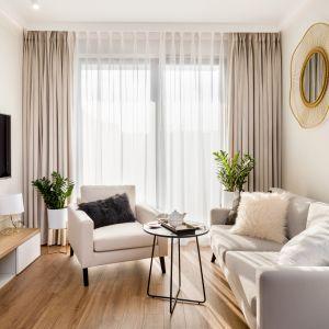 Jasnoszara sofa doskonale komponuje się z wnętrzem w stylu glamour. Projekt Joanna Nawrocka