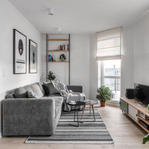 Szara sofa z welurową tapicerką przełamuje minimalistyczny wystrój. Projekt Raca Architekci. Fot. Fotomohito