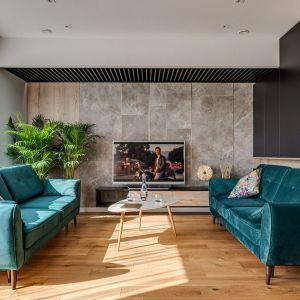 Przestronny salon urządzony prosta i nowocześnie doskonale ociepla drewniana podłoga. Projekt: Marta Kilan, Anna Kapinos, Tomasz Słomka. Fot. Radosław Sobik