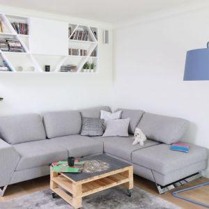 Wygodna narożna sofa to centrum strefy wypoczynkowej. Stolik z palet dodaje jej charakteru. Ciekawie prezentuje się szafka nad kanapą. Projekt: Laura Sulzik. Fot. Bartosz Jarosz