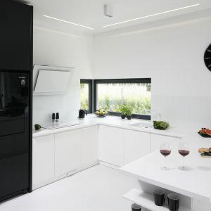Minimalistyczna kuchnia z przewagą bieli i czarnymi akcentami. Projekt Ewelina Pik, Maria Biegańska. Fot. Bartosz Jarosz