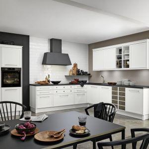 Klasyczna kuchnia z wysoką zabudową z piekarnikiem i stylowym czarnym okapem. Fot. Nolte Kuchen