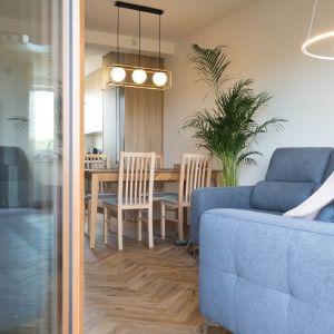 Część dzienna, jaką jest salon połączony z kuchnią to przede wszystkim ciepłe kolory drewna wpływające na wspomnianą przytulność i nieco rustykalny charakter. Projekt Nabak Architektura Wnętrz / Luxrad