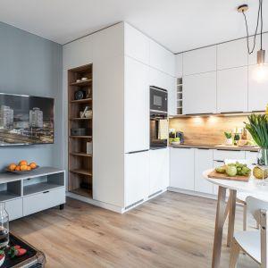 Meble kuchenne przechodzą w zabudowę regałową: Projekt i zdjęcia: pracownia KODO Projekty i Realizacje Wnętrz