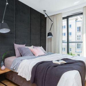 Tapicerowana ściana w ciemnym, szarym kolorze to najmocniejszy element w sypialni. rojekt: Decoroom. Fot. Pion Poziom