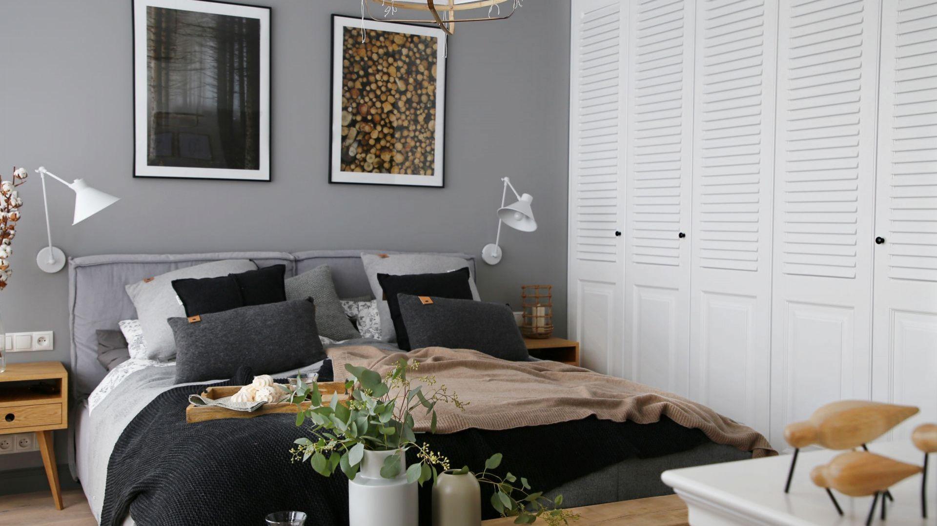 Ściana za łóżkiem wykończono szarą farbą doskonale pasujme do białych frontów szafy i jasnego wybarwienia drewna. Projekt wnętrza: SHOKO design