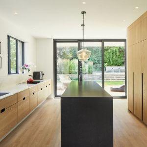 W dużej kuchni dominuje drewniana zabudowa oraz funkcjonalna wyspa kuchenna. Projekt: Salem Architecture. Zdjęcia: Phil Bernard