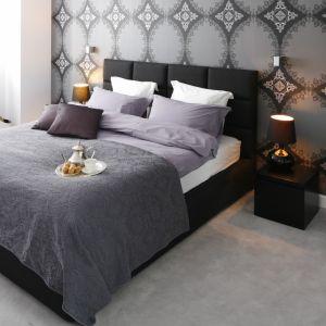 Szara tapeta z motywem delikatnej koronki stanowi efektowne tło dla nowoczesnego łóżka tapicerowanego czarną tkaniną. Projekt: Magdalena Smyk. Fot. Bartosz Jarosz.