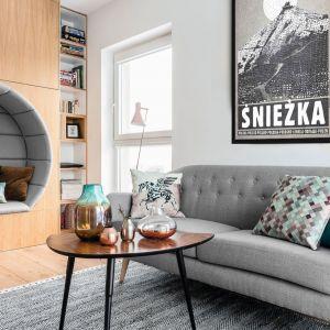 Nieduża dwuosobowa sofa na nóżkach doskonale sprawdzi się w małym salonie. Projekt: Projekt: Magdalena Bielicka, Maria Zrzelska-Pawlak, Pracownia Magma. Fot. Fotomohito