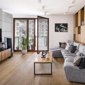 Jedna ściana w salonie wykończona została betonowymi płytami. Inną ścianą zdobi drewnianym dekoracyjny regał. Projekt: Zuzanna Kuc, ZU projektuje. Fot. Łukasz Zandecki