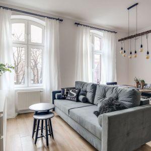 Prosta, nowoczesna kanapa oddziela strefę wypoczynkową od przestrzeni jadalni. Projekt Małgorzata Mataniak-Pakuła. Fot. Radosław Sobik