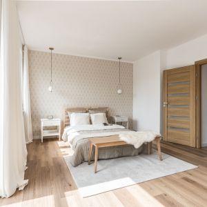 Na ścianie za łóżkiem pojawiła się łagodna tapeta. Sama rama łóżka wykonana została z naturalnego drewna. Projekt: Ewelina Matyjasik-Lewandowska. Fot. Tomasz Kazaniecki