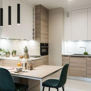 Zabudowa kuchenna aż do samego sufitu sprawia, że jest tu sporo miejsca na przechowywanie. Projekt: pracownia KODO Projekty i Realizacje