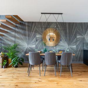 Prosty, lekki w formie stół, otoczono sześcioma krzesłami, które są idealnym tłem dla niezwykłego, okrągłego lustra w ramie imitującej promienie słońca. Projekt: Decoroom. Fot. Marta Behling, Pion Poziom