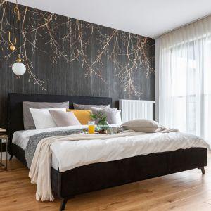 Czysta biel dobrze komponuje się z tapetą wpadającą w grafit z motywem złotych gałązek, która zdobi jedną ze ścian, powielając botaniczny klimat obecny w całym mieszkaniu. Projekt: Decoroom. Fot. Marta Behling, Pion Poziom