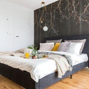 Na obitym czarnym welurem łóżku piętrzą się poduszki w bieli i w naturalnej tonacji ziemi. Projekt: Decoroom. Fot. Marta Behling, Pion Poziom