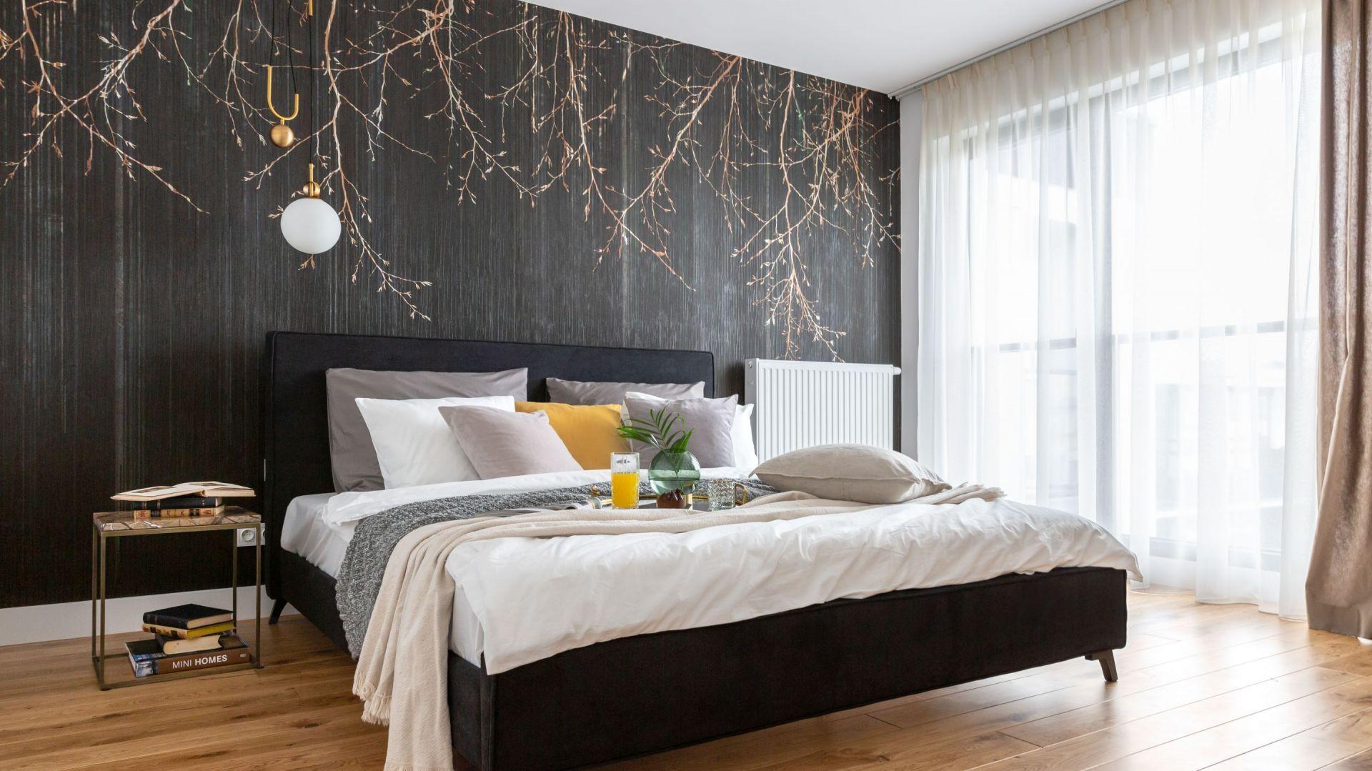 Biel i drewno dobrze komponują się z tapetą wpadającą w grafit z motywem złotych gałązek, która zdobi ścianę za łóżkiem. Projekt: Decoroom. Fot. Marta Behling, Pion Poziom