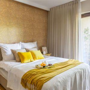 Ścianę za łóżkiem zdobi tapeta w mocnym, wyrazistym kolorze. Jej wzór jest jednak bardzo spokojny, dzięki czemu ściana prezentuje się bardzo ładnie. Projekt: Dorota Kudła. Fot. Pion Poziom
