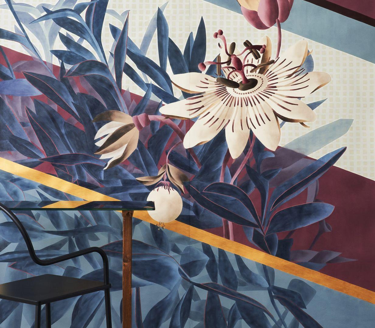 """""""Passiflora"""", czyli kwiat męczennicy z owocami, jest niekwestionowanym bohaterem tej tapety. Ponadwymiarowy design łączy się tu z bujną paprocią poprzez naprzemienne nakładanie się i przenikanie elementów poszczególnych planów. Inspiracją dla tła jest świat tekstyliów, gdzie geometryczne mikro wzory występują naprzemiennie z szerokimi ukośnymi paskami. Na jej wyjątkowy wygląd wpływają dodatkowo ręcznie haftowane detale, które nadają kwiatom aspekt pełnej trójwymiarowości. Fot. Mood-Design"""