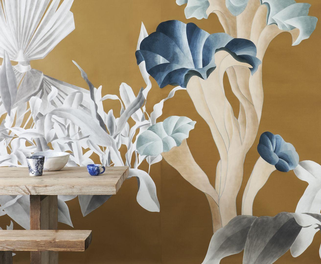 """Tapeta """"Formosa"""" nawiązuje do świata fotografii, w którym kolorowe obramowanie służy jako tło dla hipotetycznego mise en scène sennej i surrealistycznej inscenizacji. Paprocie i egzotyczne rośliny stanowią granicę dla znajdujących się na pierwszym planie gigantycznych i pozaziemskich grzybów o jasnych i nienaturalnych kolorach. Trójwymiarowy efekt sugerują nie tylko same dekoracje, ale także ręczny haft widoczny na grzybach. Fot. Mood-Design"""