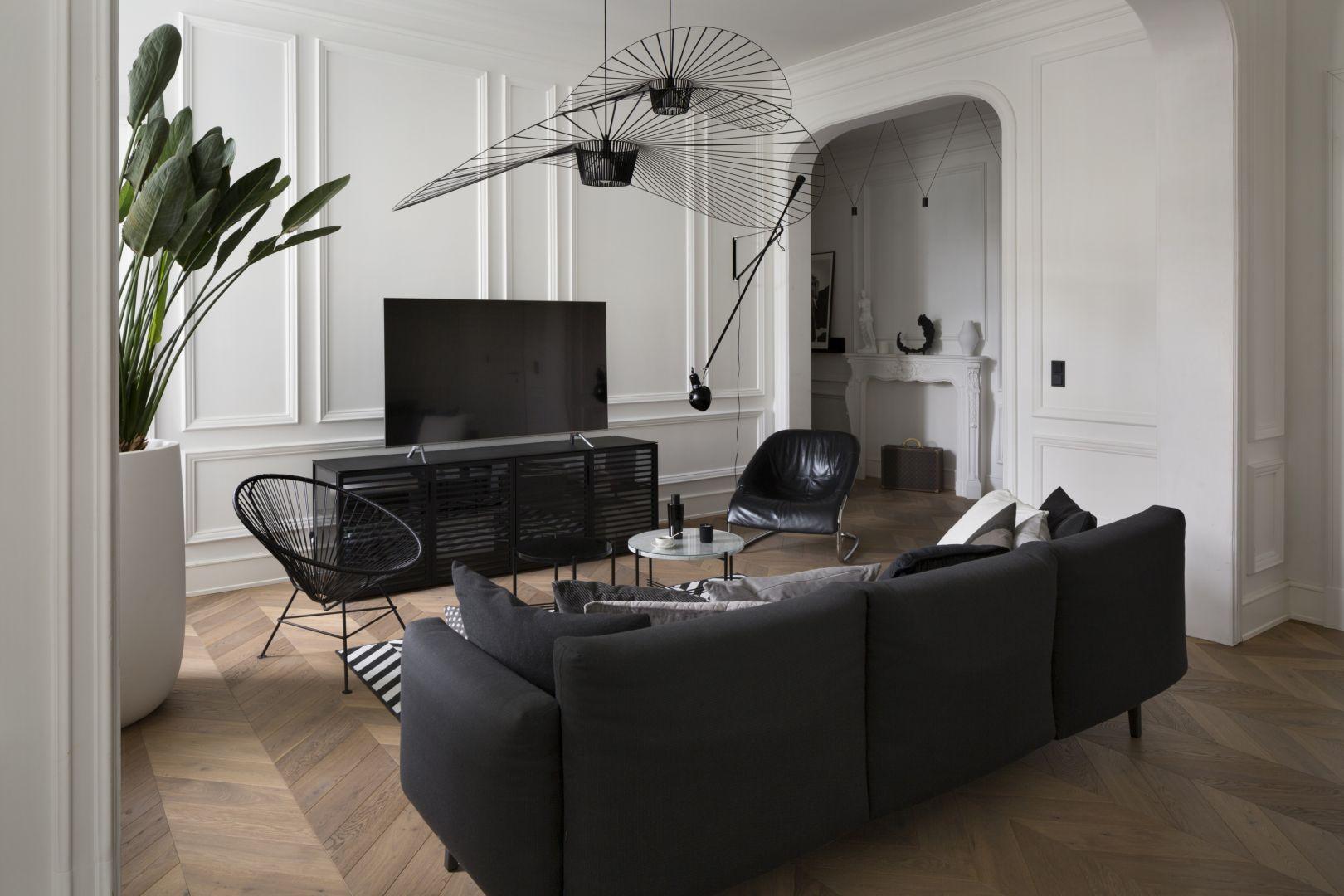 Drewniana podłoga  ułożona w jodłę francuską prowadzi nas do salonu z kuchnią. Projekt Goszczdesign. Fot. Piotr Mastalerz
