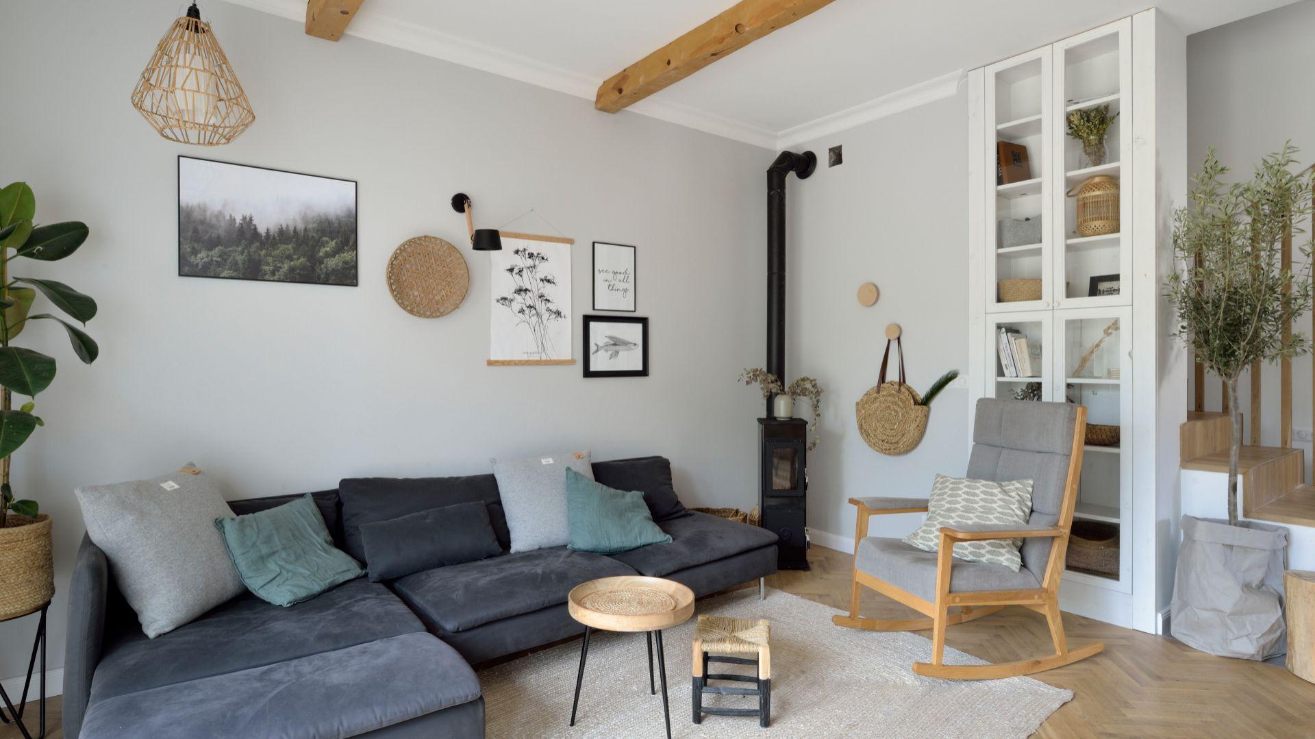 Ścianę za kanapą wykończono jasną, szara farbą. Na jej tle pięknie prezentuje się obraz i grafiki. Projekt: SHOKO.design. Fot. Łukasz Nowosadzki, Archilens.pl