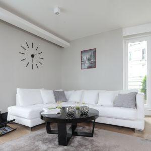 Ściana za kanapą pomalowana została na jasny, szary kolor, który doskonale pasuje do białej kanapy. Projekt: Magdalena Kostrzewa-Świątek, Agnieszka Zaremba. Fot. Bartosz Jarosz
