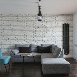 Ścianę za kanapą wykończono cegłą w białym kolorze. Projekt: MAFgroup. Fot. Emi Karpowicz