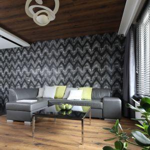 Ścianę za kanapą wykończono dekoracyjną tapetą. Jej mocny wzór i ciemny kolor stanowią mocny element w salonie. Projekt: Marta Kilan. Fot. Bartosz Jarosz