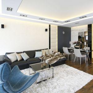Ścianę za kanapą wykończono jasnym kolorem. Z dwóch stron zdobią ja subtelne, pikowane panele. Projekt: Agnieszka Hajdas-Obajtek. Fot. Bartosz Jarosz