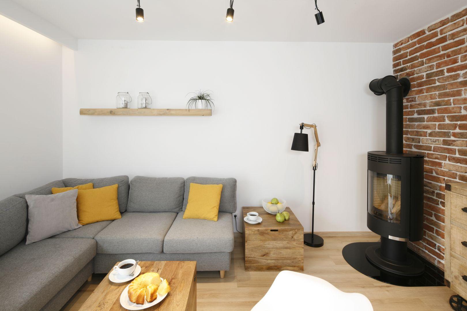 Salon jest urządzony prosto i nowocześnie. Przytulności dodaje mu drewno oraz cegła. Projekt: Katarzyna Uszok. Fot. Bartosz Jarosz