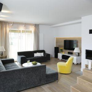 Ciemne kanapy i żółty fotel doskonale prezentują się w otoczeniu bieli i drewna. Projekt: Małgorzata Galewska. Fot. Bartosz Jarosz