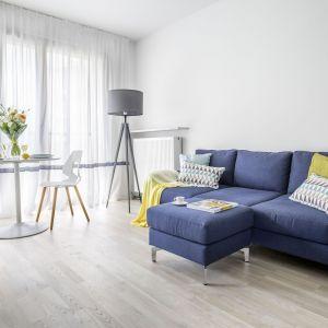 W sposób umowny inną funkcję pomieszczenia wyznaczą kolor czy faktura ściany, podłogi, oświetlenie lub po prostu dywan pod stolikiem kawowym z pufami i kanapą. Projekt Decoroom. Fot. Pion Poziom