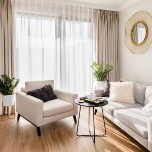 Beżowe zasłony idealnie pasują do jasnego, niedużego salonu. Projekt: Joanna Nawrocka. Fot. Łukasz Bera