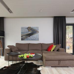 Ciemne brązowe zasłony dobrano do koloru kanapy oraz podłogi. Projekt: Laura Sulzik. Fot. Bartosz Jarosz