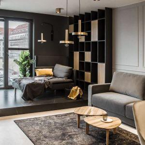 Dwa, drewniane stoliki doskonale pasują do drewniej podłogi i szarej kanapy. Projekt i zdjęcia: studio Mauve