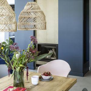 W salonie połączonym z jadalnią reprezentowany przez wygodny, atramentowy narożnik, pełen wdzięku jadalniany stół z drewnianym blatem czy pasujące tu jak ulał kubełkowe krzesła o zaoblonych formach, w delikatnych odcieniach różu, szarości i beżu. Projekt Malwina Morelewska. Foto Yassen Hristov