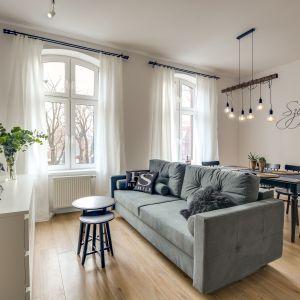 Szara sofa organizuje przestrzeń do wypoczynku. Projekt Małgorzata Mataniak-Pakuła. Fot. Radosław Sobik