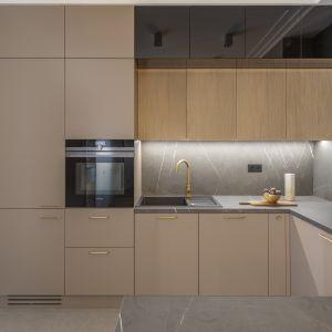 W kuchni postawiono na prostą zabudowę wzbogaconą o metalowe nogi w kolorze złota, które wprost urzekają dyskretną elegancją. Projekt Decoroom Fot. Marta Behling Pion Poziom