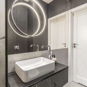 W łazience głównym elementem dekoracyjnym jest oświetlenie nad umywalką. Projekt Decoroom Fot. Marta Behling Pion Poziom